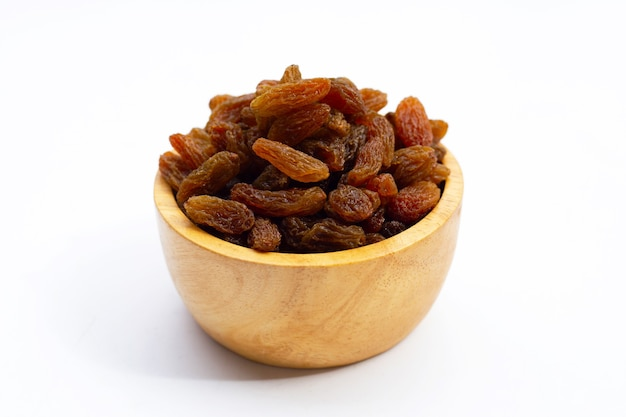 Dried grape raisins in wooden bowl on white background