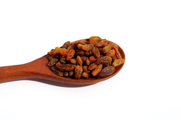Dried grape raisins in wooden spoon on white background