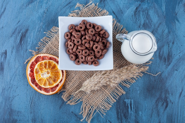 Dried grapefruit, a bowl of corn rings and a jug of milk on a towel , on the blue surface.