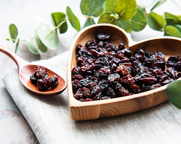 Dried grapes, raisins on a grey concrete surface Premium Photo