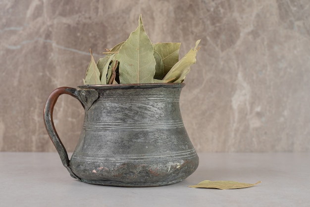 Dried green bay leaves in an ethnic pot.