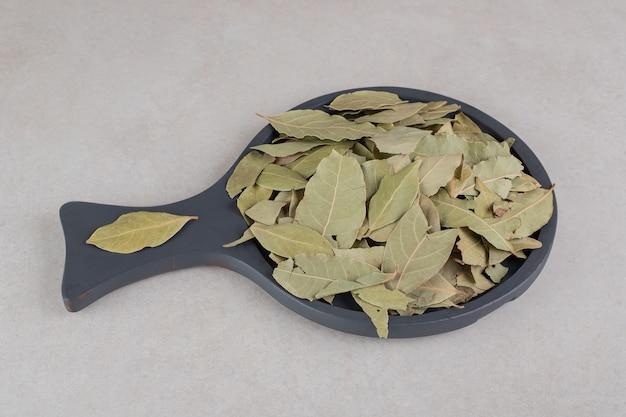 木製の大皿に乾燥した緑の月桂樹の葉。