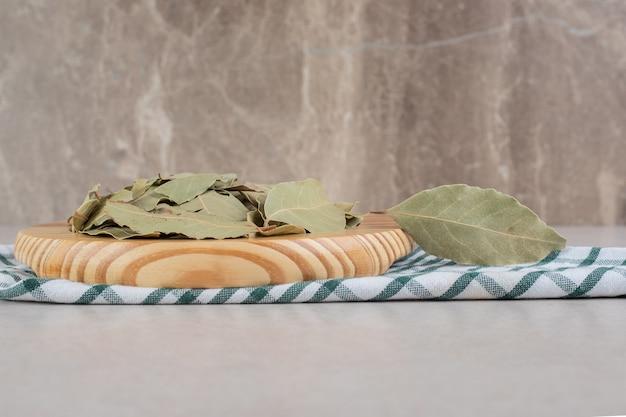 Сушеные зеленые лавровые листья на деревянном блюде.