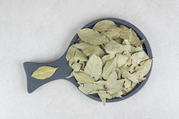 Foglie di alloro verdi essiccate su un piatto di legno.