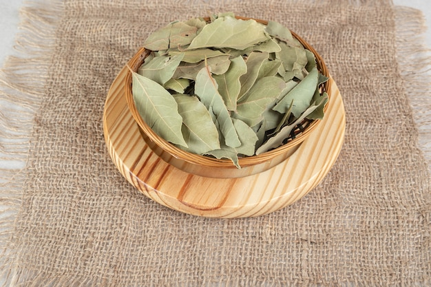Dried green bay leaves on a wooden plate.