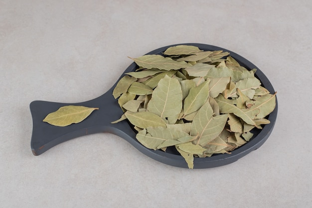 Dried green bay leaves on a wooden platter.