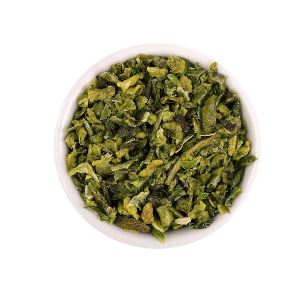 白い背景で隔離のボウルにシードと乾燥した緑のパプリカフレーク。ハラペーニョ、ハバネロ、唐辛子のみじん切り。スパイスとハーブ。上面図。