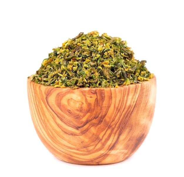 白い背景で隔離のオリーブボウルに種と乾燥した緑のパプリカフレーク。ハラペーニョ、ハバネロ、唐辛子のみじん切り。スパイスとハーブ。