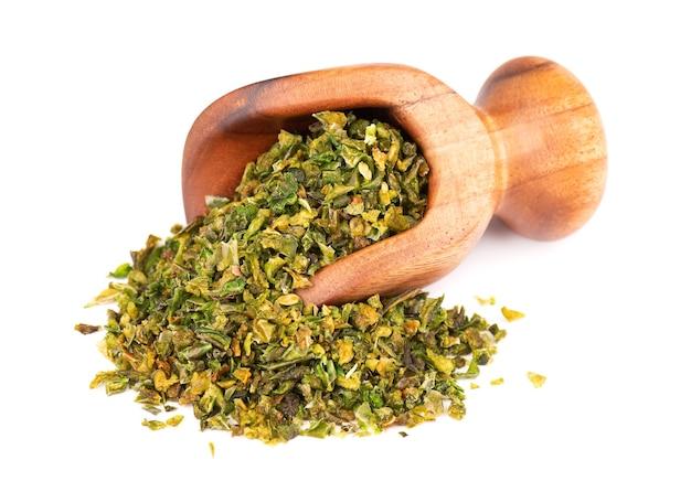 白い背景で隔離の木製スクープの種子と乾燥した緑のパプリカフレーク。ハラペーニョ、ハバネロ、唐辛子のみじん切り。スパイスとハーブ。上面図。