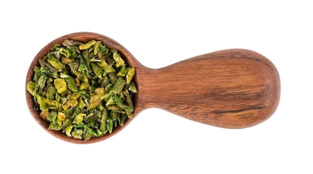 白い背景で隔離、木のスプーンで種子と乾燥した緑のパプリカフレーク。ハラペーニョ、ハバネロ、唐辛子のみじん切り。スパイスとハーブ。上面図。