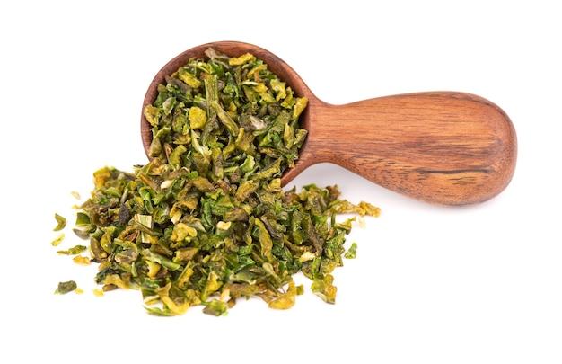 白い背景で隔離、木のスプーンで種子と乾燥した緑のパプリカフレーク。ハラペーニョ、ハバネロ、唐辛子のみじん切り。スパイスとハーブ。