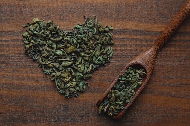 Dried green tea leaves in the shape of heart and spoon on a wooden background