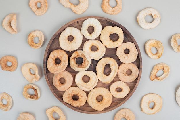 Сушеное здоровое яблоко на деревянной тарелке