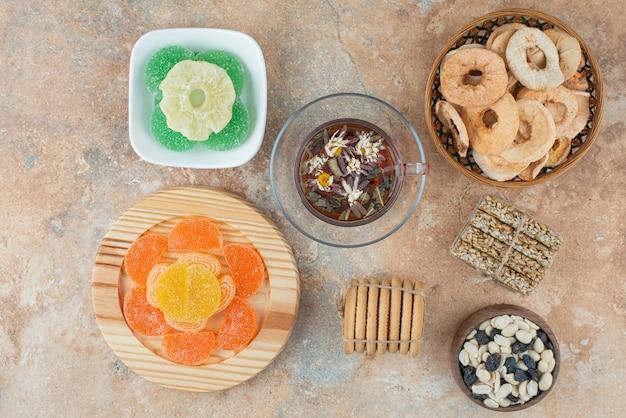 Сушеные полезные фрукты с мармеладом и чашкой травяного чая