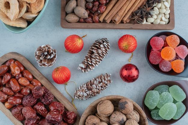 Сушеные здоровые фрукты на деревянной тарелке с елочными игрушками. фото высокого качества