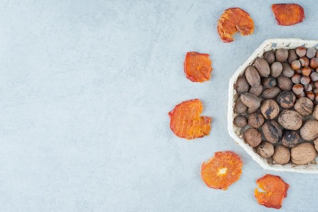 Сушеный здоровый апельсин с корзиной, полной орехов. фото высокого качества