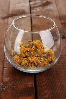 Сушеные травы в стеклянной таре на деревянном столе крупным планом