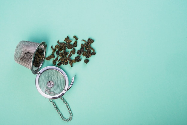 Dried herb tea spilled from the tea strainer on blue backdrop