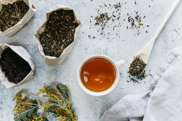 Dried herbal tea with tea cup on concrete backdrop