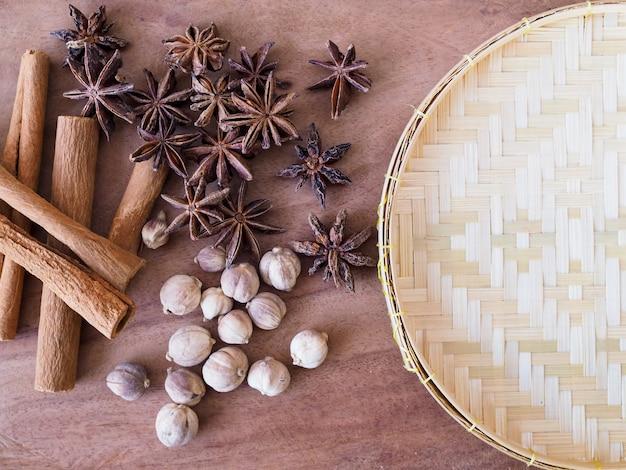 木製のテーブルに竹織りバスケットにコピースペースを持つハーブとスパイスを乾燥させます。