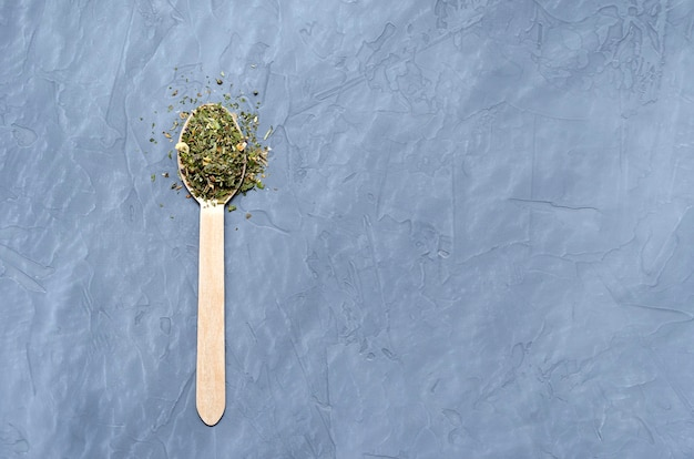 Dried herbs and spices in a wooden spoon on a gray