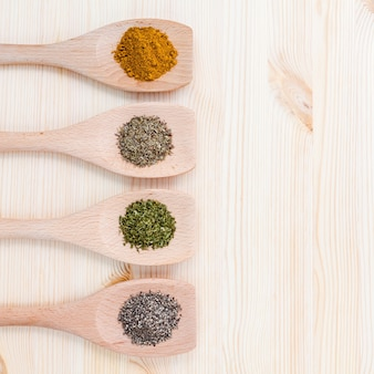 Dried herbs and spices on wooden table with copy space.