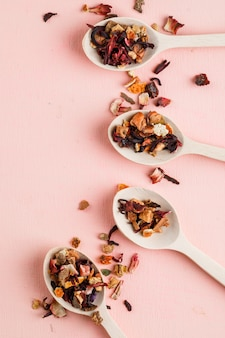 Dried herbs in wooden spoons on a pink.
