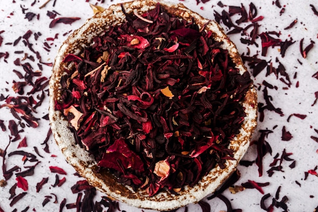Dried hibiscus leaves scattered in a ceramic plate, close-up, top view