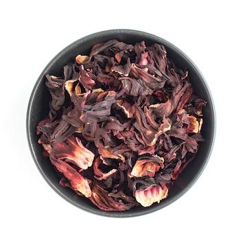 白で隔離された暗いボウルで乾燥したハイビスカスの花びら。赤茶、カルカデ。上面図。