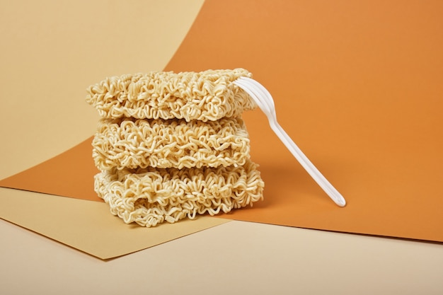 Dried instant noodles on beige and brown table copy space