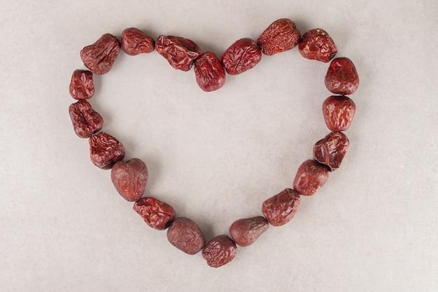 Bacche di giuggiola essiccate a forma di cuore su cemento.