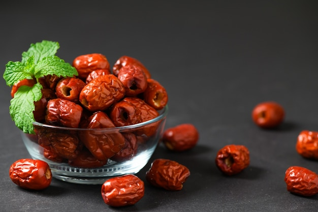 Dried jujube, chinese dried red date fruit with mint leaves in glass cup on black background,herbal fruits.