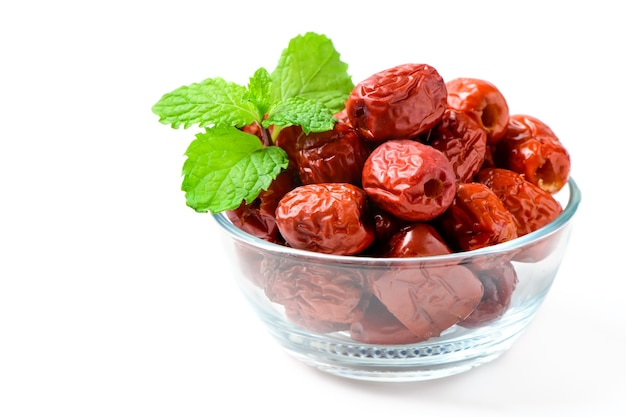 Dried jujube, chinese dried red date fruit with mint leaves in glass cup isolated on white,herbal fruits.