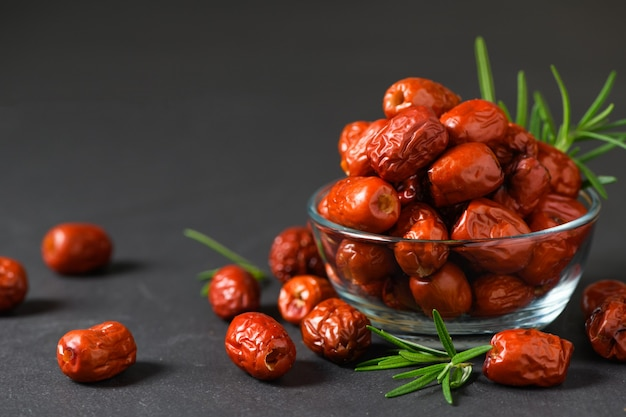 Dried jujube, chinese dried red date fruit with rosemary leaf in glass cup on black background, herbal fruits.