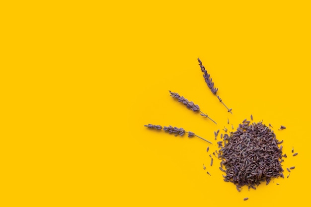 Dried lavender beautifully laid out on a yellow background, top view, with copyspace.