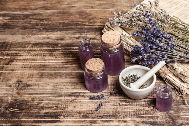 Dried lavender flowers in a in a mortar and pestle with bottle of essential lavender oil