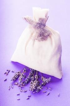 花と紫色のbacgkroundの上に乾燥したラベンダーの小袋