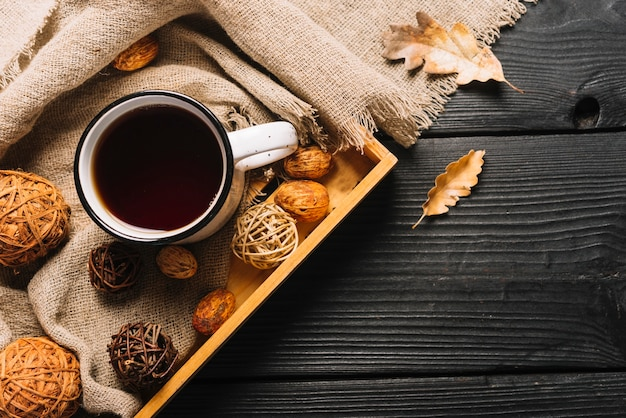 Dried leaves and fabric near tray with beverage