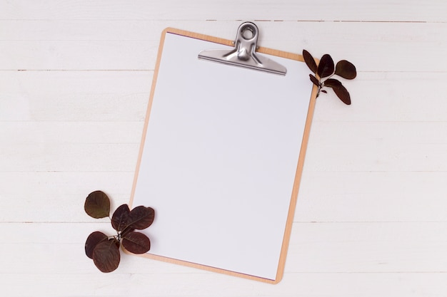 Dried leaves with white mock-up clipboard