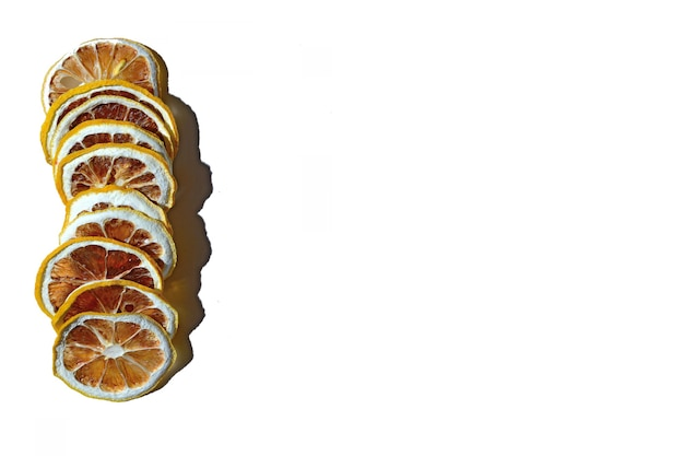 흰색 배경에 서로의 위에 누워 말린 레몬 조각. 외딴