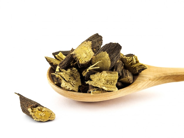 Dried licorice or liquorice roots lie in a wooden spoon on a white