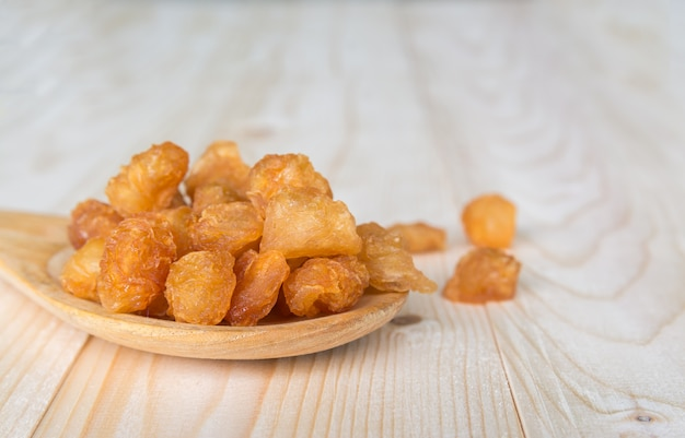 Dried longan with wooden spoon and table