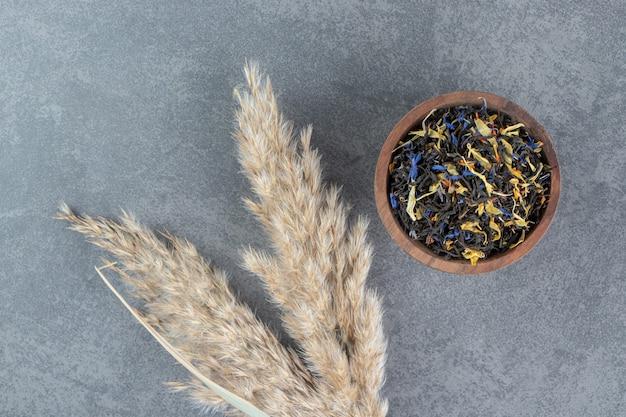 Tè sfusi secchi con grano su una ciotola di legno