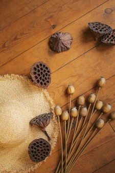 Dried lotus and poppy seed pods and straw hat on an old wooden floor.