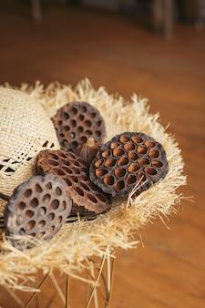 Сушеные стручки семян лотоса на соломенной шляпе с полями в интерьере.