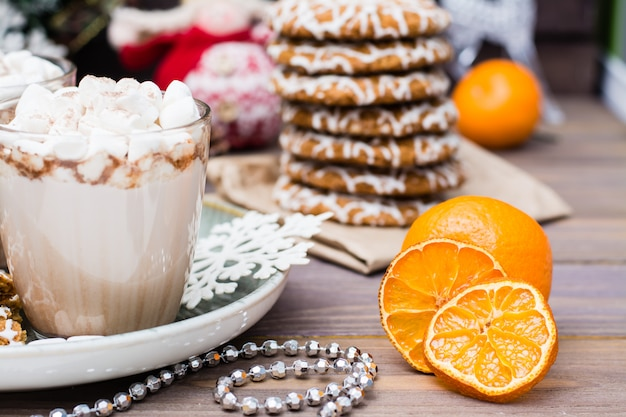 Dried mandarin slices, hot cocoa with marshmallows and christmas cookies on the table in christmas decorations