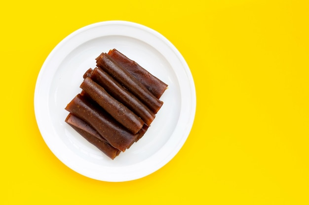 Dried mango paste in white plate on yellow background.