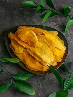 Dried mango slices. in a black plate on a dark background. nearby are branches of greenery. view from above.