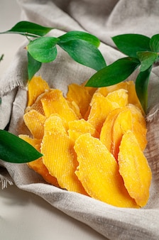 Dried mango slices on a linen towel. nearby are branches of greenery. close-up. macro