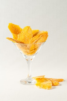 Dried mango slices. in a martini glass. light background.